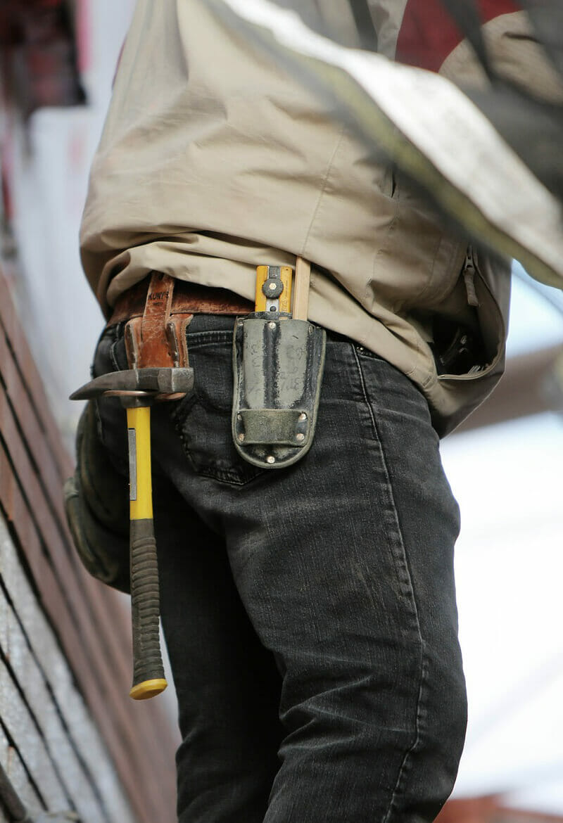 Construction worker with multiple tools tucked into his pants