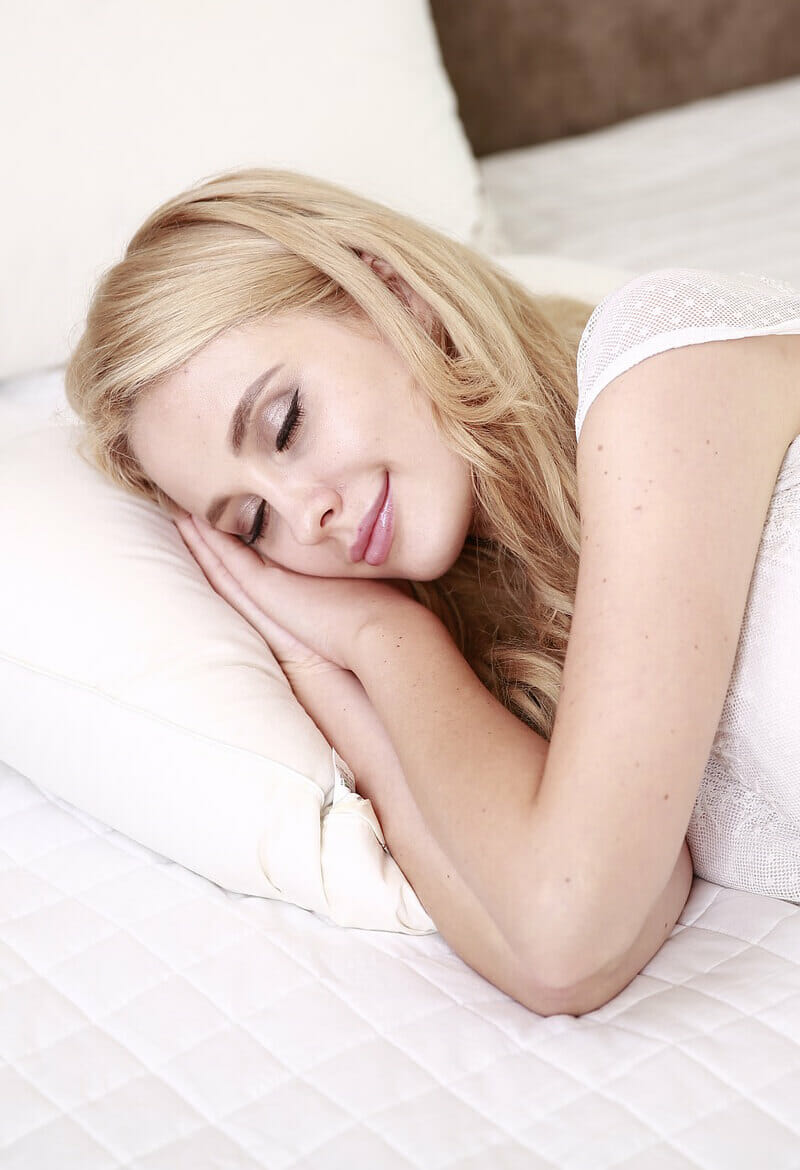 Blond girl sleeps peacefully in her bed