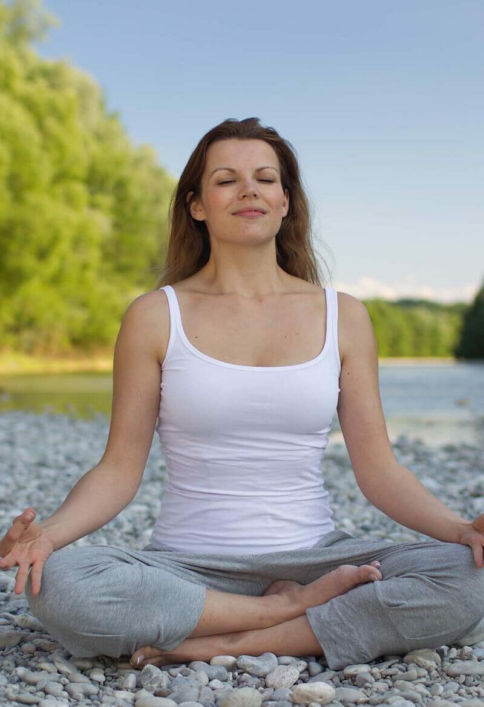 Woman performs yoga on rocks by a lake